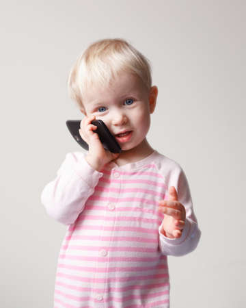 Cute adorable white Caucasian blond baby with blue eyes talking expressively emotionally over mobile cell phone with funny expression on her face, new technology future generation concept, on light background photo