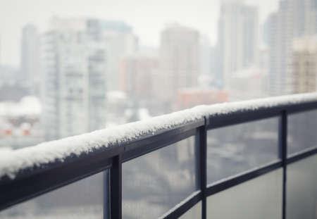Baranda del balcón negro con vidrio, nieve del invierno, fondo ciudad ciudad borrosa, con copia espacio para el texto, entonado con filtro Foto de archivo