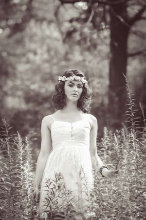 Black and white portrait of beautiful white Caucasian girl with long wavy curly hair and flowers chaplet on head. Attractive young woman model in park outside, country village hippie style