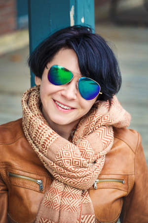 Portrait of smiling middle aged caucasian dark haired brunette woman with short bob hair  in sunglasses wearing light brown leather jacket and scarf outside, autumn fall theme concept