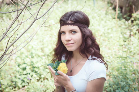 Portrait of beautiful white Caucasian young woman girl with long red brown hair in white short top, wearing brown hippie style headband, holding small yellow flowers dandelions in forest park outside on summer spring day, smiling looking directly in camer Stock Photo