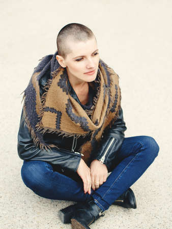 artsy: Portrait of beautiful Caucasian white young bald girl woman sitting on ground outside with shaved hair head in jacket, scarf shawl, jeans, looking away, toned with filters in yellow color