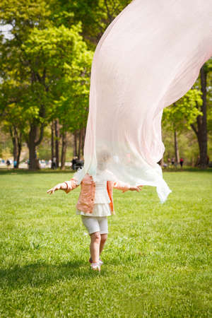 Portrait of a cute adorable baby toddler girl playing on field meadow on bright sunny summer day with mom who covers her with transparent light cloth scarf making her look like a ghost, happy childhood family activity lifestyle concept