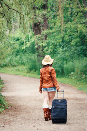 Portrait of Caucasian girl woman in leather jacket, blue denim shorts, straw hat, standing walking on country road wild forest with travel bag with her back to camera, wanderlust adventure vacation Stock Photo