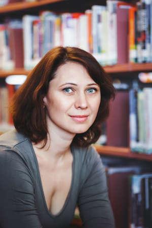 portrait Gros plan de sourire âge mûr femme d'âge mûr étudiant dans la bibliothèque à la recherche à huis clos, enseignant profession de bibliothécaire, de retour au concept de l'école