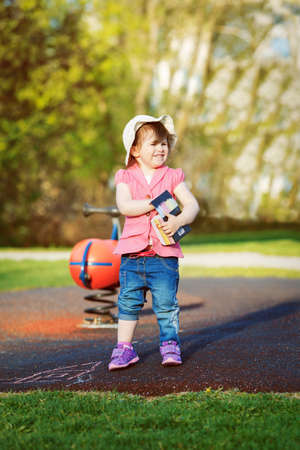 three years old: Colorful portrait of a cute smiling little girl toddler child, two or three years old, in pink jacket, blue jeans, white hat standing on playground holding a box of chalk to draw,  concept of childhood lifestyle
