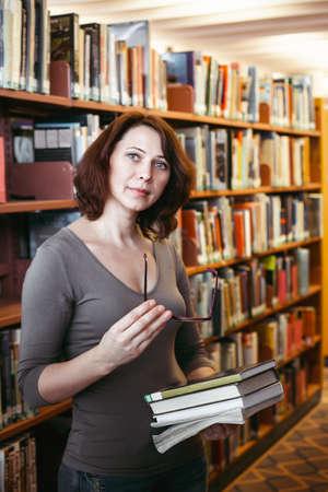 Portrait d'âge moyen brune mature femme de race blanche étudiant avec des lunettes dans le livre de maintien bibliothèque, en regardant directement la caméra, professeur profession de bibliothécaire, de retour au concept de l'école
