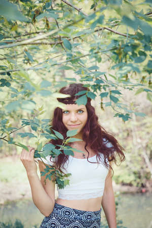 Portrait of beautiful white Caucasian young woman girl with long brown red wavy hair wearing white short top, with brown hippie style headband standing in forest park outside in summer spring, smiling looking directly into camera