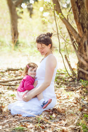 tummy time: Portrait of caucasian pregnant mother in white dress sitting on ground in park outside among blooming cherry trees, with daughter in pink clothes sitting on her laps  on sunny spring summer day