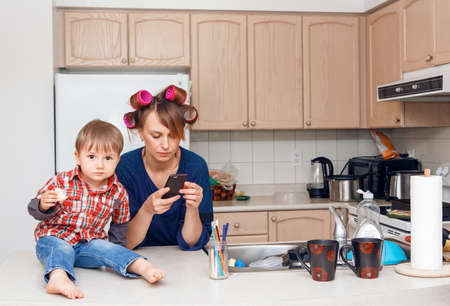 haircurlers: Busy white Caucasian young woman mother housewife with hair-curlers in her hair taking pictures of things, objects, utensils in her kitchen, her kid child son boy sitting beside her eating a cookie, smiling and playing, crazy busy life Stock Photo