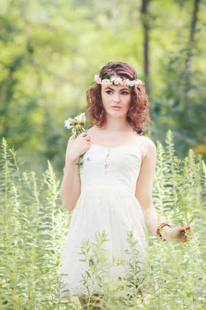 Beautiful white Caucasian girl with hazel eyes, long wavy curly hair and flowers chaplet on head. Attractive young woman model in park outside, country village hippie style