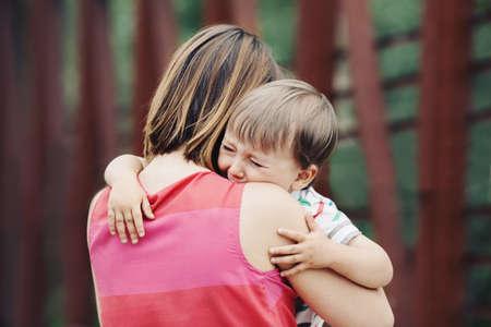 Portret van een jonge blanke vrouw moeder troost haar buiten huilende kleine peuter jongen zoon in park op zomerse dag, ouderschap lifestyle concept