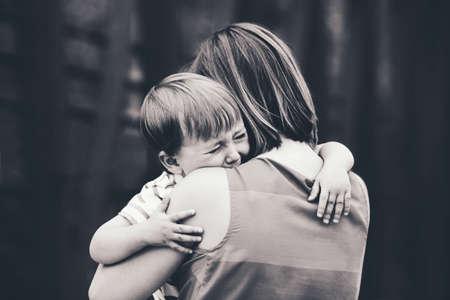 Zwart-wit portret van de jonge blanke vrouw moeder troost haar buiten huilende kleine peuter jongen zoon in park op zomerse dag, ouderschap lifestyle concept Stockfoto