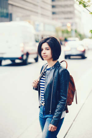 Portrait of beautiful young Caucasian latino girl woman with dark brown eyes and short dark hair in blue jeans, leather biker jacket with backpack standing in street outside