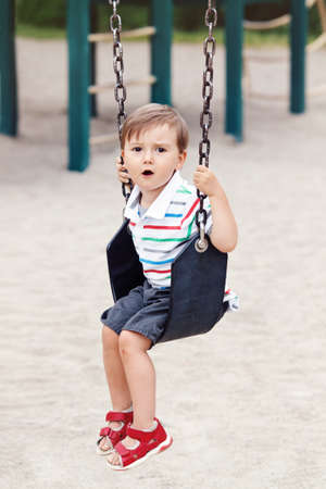 Portrait of sad upset worried little small boy toddler in tshirt and jeans shorts on swing on backyard playground outside on summer day, childhood lifestyle concept