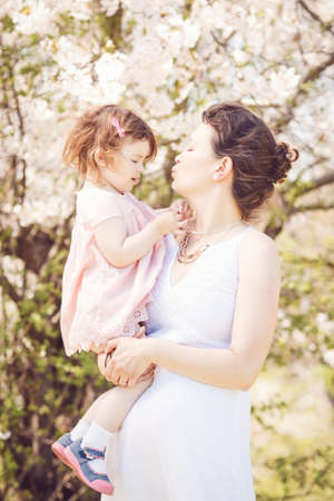 tummy time: Portrait of caucasian pregnant mother in long white dress holding and kissing her daughter in pink clothes on spring summer day in park outside among blooming cherry trees