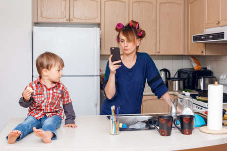 female child: Busy white Caucasian young woman mother housewife with hair-curlers in her hair taking pictures of things, objects, utensils in her kitchen, her kid child son boy sitting beside her eating a cookie, smiling and playing, crazy busy life Stock Photo