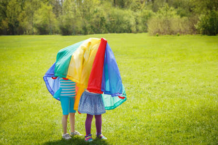 Two adorable cute girls standing in summer green field meadow on a bright sunny day outside under parachute playing hiding, having fun, sports recreation child games activities concept