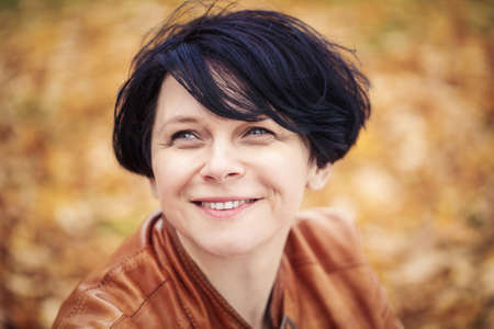 Closeup portrait of middle aged caucasian dark haired brunette woman with short bob hairstyle in light brown leather jacket  looking up smiling outside in autumn fall park