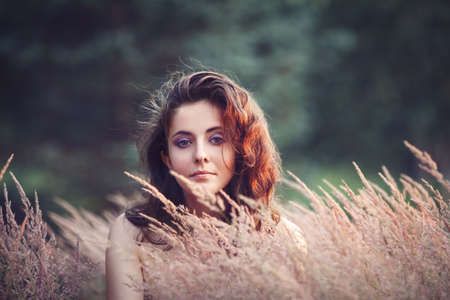 innocent: Portrait of beautiful  innocent Caucasian adult girl woman with long dark red brown hair, hazel eyes in park field outside on sunset in golden hour looking in camera