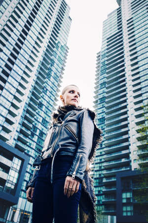 state of mood: Wide angle low point of view, portrait of beautiful Caucasian white young bald girl woman with shaved hair head in leather jacket and scarf looking away, spiritual mood state of mind Stock Photo
