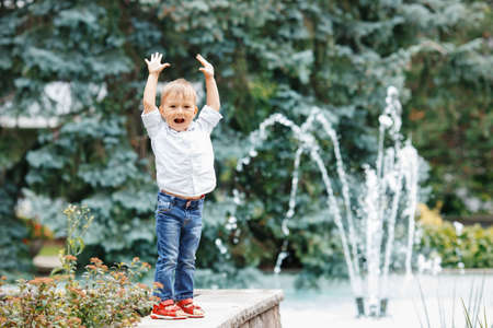 toddler boy: Portrait of cute adorable funny Caucasian  little boy toddler in white shirt and blue jeans playing laughing smiling having fun by fountain in summer outside Stock Photo