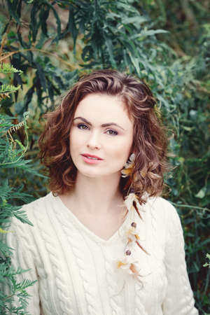 eyes hazel: Portrait of beautiful smiling white Caucasian girl woman with long curly hair hazel eyes, in white sweater, feather earring hipster hippie style, among green tree leaves, toned with  vsco filters