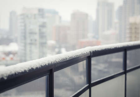 balcony: Balcony black railing with glass, winter snow, blurry city town background with copy space for text, toned with filter Stock Photo