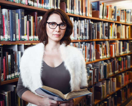 librarian: Portrait of middle age mature brunette Caucasian woman student with glasses in library holding book, looking directly in camera, teacher librarian profession