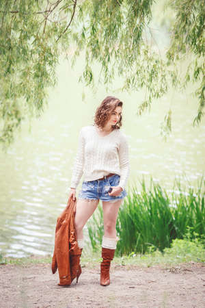 leather boots: Portrait of beautiful Caucasian young girl woman with wavy curly hair in white sweater,  blue denim shorts and tall leather boots, holding brown jacket, posing outside in park, summer autumn look