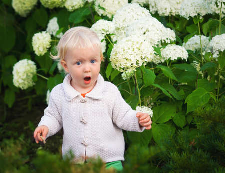 Cute adorable surprised crying screaming baby boy girl child standing among flowers, lifestyle, happy childhood concept