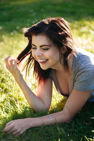 Closeup portrait of beautiful smiling young Caucasian woman with red black hair, lying on grass outdoors, laughing showing teeth, natural beauty youth look