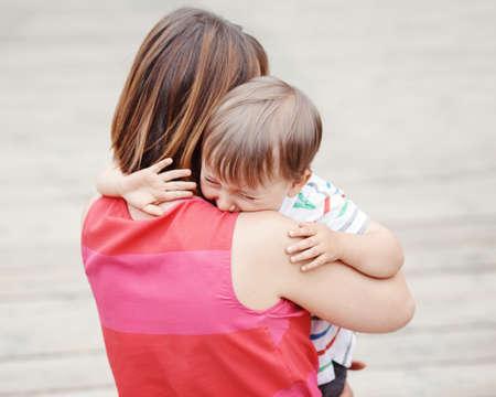 夏の日、親のライフ スタイル コンセプトに泣いている小さな幼児少年で彼女の息子の外公園を慰め若い白人女の母の肖像画