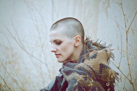 Portrait des traurigen schönen kaukasischen weiß kahles Mädchen Frau mit rasierten Haar Kopf in Lederjacke und Schal shaw Wegschauen