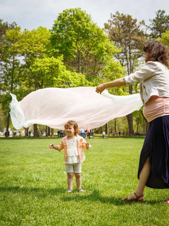 Portrait of a cute adorable baby toddler girl playing on field meadow on bright sunny summer day with mom who covers her with transparent light cloth scarf making her look like a ghost, happy childhood family activity concept