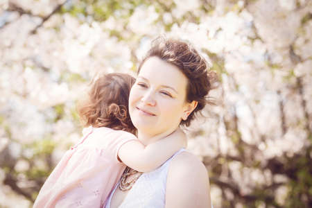 mum and daughter: Close up portrait of caucasian mother in white dress holding hugging her daughter in pink clothes smiling on sunny spring summer day in park outside
