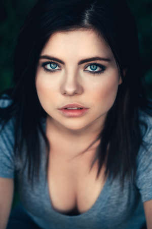 Closeup portrait of beautiful young sexy Caucasian woman with black hair, blue eyes, looking in camera, sitting outdoors, toned with filters, natural beauty youth look, top above view