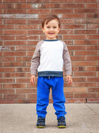 Portrait of a cute adorable little boy toddler two or three years old standing by brick wall and smiling, laughing, posing outside in the street