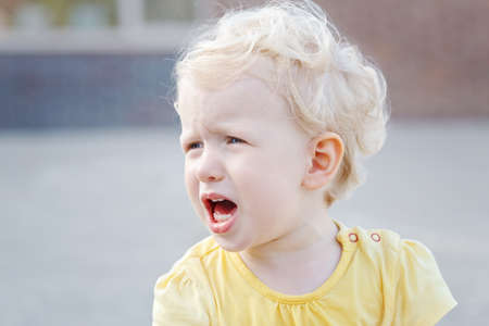 Close up portrait of crying screaming little white blond Caucasian toddler boy girl in yellow clothes outside on summer day
