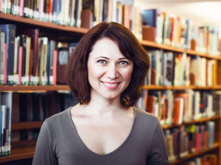 portrait Gros plan de sourire heureux d'âge moyen âge mûr étudiant femme dans la bibliothèque de regarder directement à huis clos, enseignant profession de bibliothécaire, de retour au concept de l'école