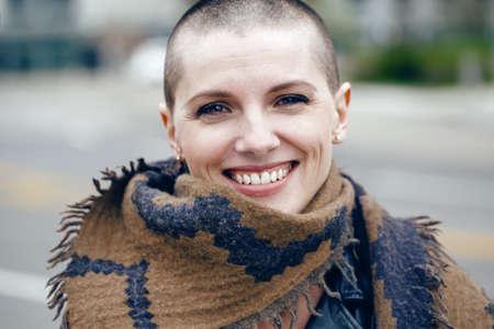 Close-upportret van gelukkige glimlachende lachende mooie Kaukasische witte jonge kale meisjesvrouw met geschoren haarhoofd in leerjasje en sjaalsjaal die in camera kijken