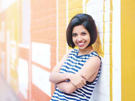 Portrait of beautiful smiling young hipster latin hispanic girl woman with short hair bob, in blue white striped tshirt, leaning on brick wall in city looking in camera