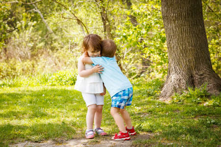 Portrait of two cute adorable baby children toddlers hugging and kissing each other, love friendship in childhood concept, best friends forever Stok Fotoğraf