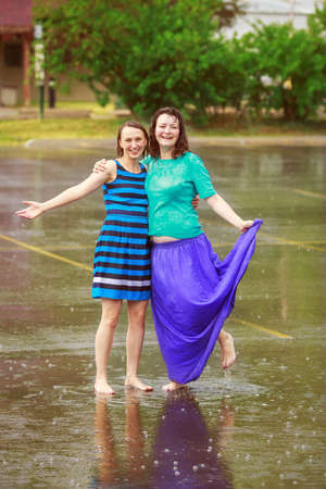 rain wet: Portrait of two happy girl friends jumping in puddles during the rain thunderstorm on a bright summer day outside, sports recreation leisure concept, friendship