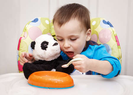Close-up portrait of cute adorable little boy toddler two years old sitting in high chair in kitchen eating meal lunch dinner using fork and feeding his panda soft plush toy