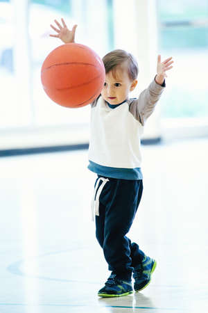 Cute adorable little small white Caucasian child toddler boy playing with ball in gym, having fun, healthy lifestyle childhood concept Archivio Fotografico
