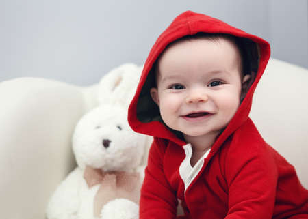 Portrait of cute adorable Caucasian smiling laughing baby boy girl with black brown eyes in red hoodie shirt sitting in chair with toy looking directly in camera
