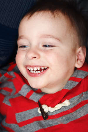 hilarious: Close-up portrait of cute funny hilarious white Caucasian little boy toddler lying on bed and laughing out loud showing his teeth looking away from camera Stock Photo