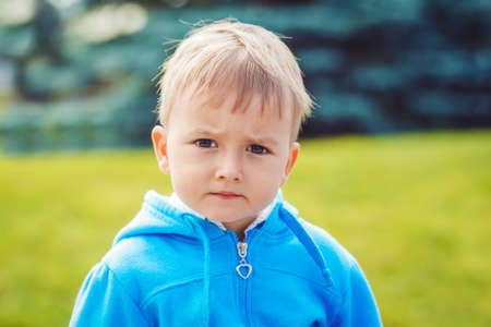 mimo: Closeup portrait of cute young Caucasian little boy with blond hair and dark brown eyes with funny face expression in blue hoodie outside in park on summer day, backlit with sun from behind, rim light of his figure