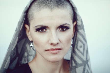 Portret van trieste mooie blanke witte jonge kale meisje vrouw met geschoren haar hoofd, sjaal cover, kijken in de camera, afgezwakt met Instagram filters in blauwgroene kleur